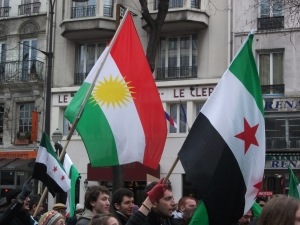 The flag of the Kurdish people, whose rights are largely unrecognized in all four countries of the Middle East where native Kurds can be found, alongside that of the Syrian opposition movement during a March 2013 demonstration in Paris, France.