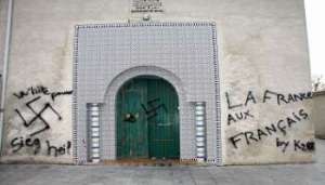 The front door of a mosque in France in 2009, covered by racist and neo-Nazi graffiti. Over the last five years anti-Islam acts have soared in the country, hitting an all-time high in the wake of the terror attack against the weekly satirical newspaper Charlie Hebdo of January 7, 2015. (C) Thierry Antoine/AFP