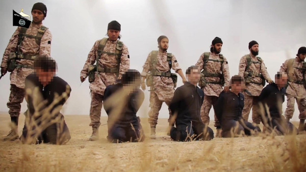 An image grab taken from a propaganda video released on November 16, 2014 by al-Furqan Media allegedly shows members of the Islamic State jihadist group preparing the simultaneous beheadings of at least 15 men described as Syrian military personnel. In the highly choreographed sequence, jihadists march the prisoners by a wooden box of long military knives, each taking one as they pass, before forcing their victims to kneel in a line and decapitating them. (C) AFP PHOTO