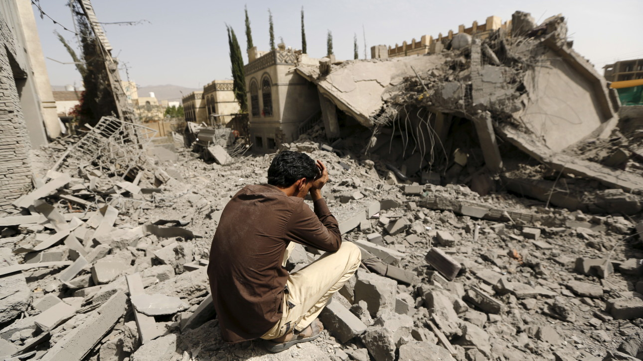 Guard sits on the rubble of the house of Brigadier Fouad al-Emad, an army commander loyal to the Houthis, after air strikes destroyed it in Sanaa, Yemen
