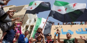 Protesters carry opposition flags and chant slogans during an anti-government protest in the rebel-held town of Dael
